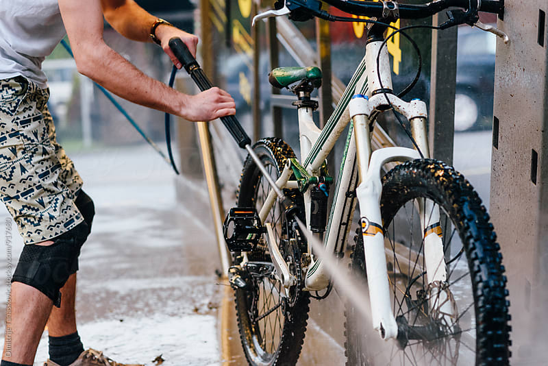 Man washing mountain bike by Dimitrije Tanaskovic for Stocksy United