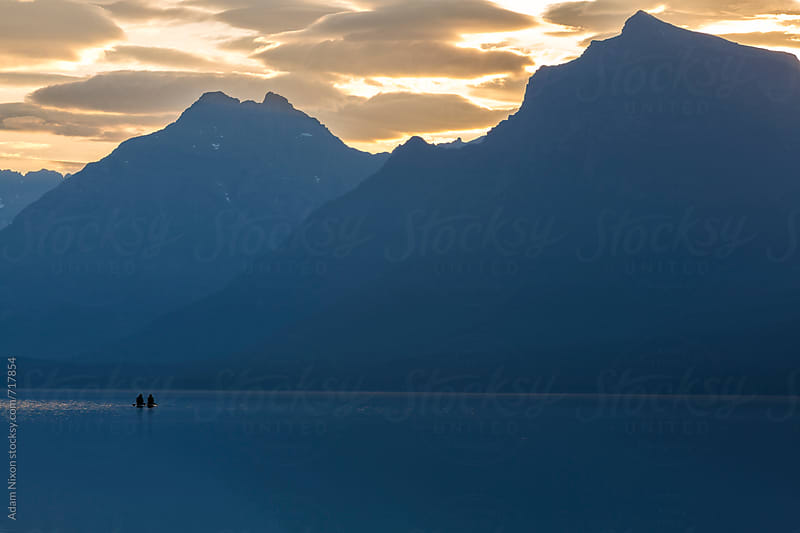 Silhouette of anonymous paddle boarders on a lake by Adam Nixon for Stocksy United