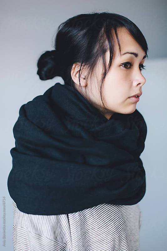 A profile of a young asian woman in a big scarf by Ania Boniecka for Stocksy United