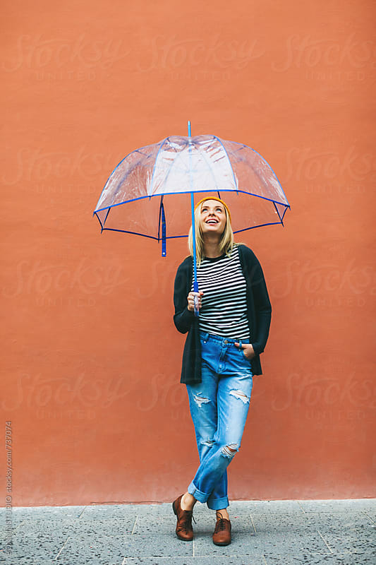 Smiling woman holding an umbrella in front of an orange wall. by BONNINSTUDIO for Stocksy United