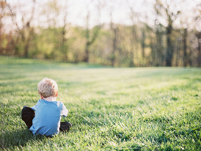 boy sitting in the grass with beautiful light by Meghan Boyer for Stocksy United