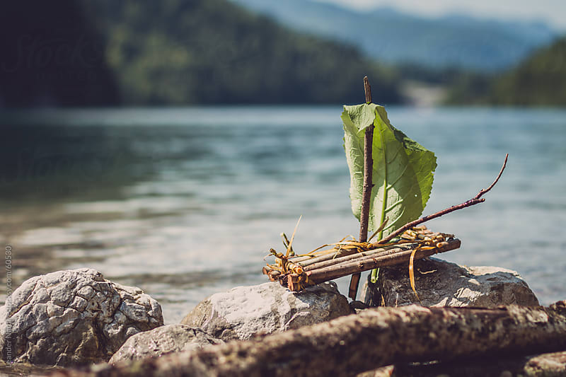 selfmade raft with a leaf agrounded on some rocks by Leander Nardin for Stocksy United