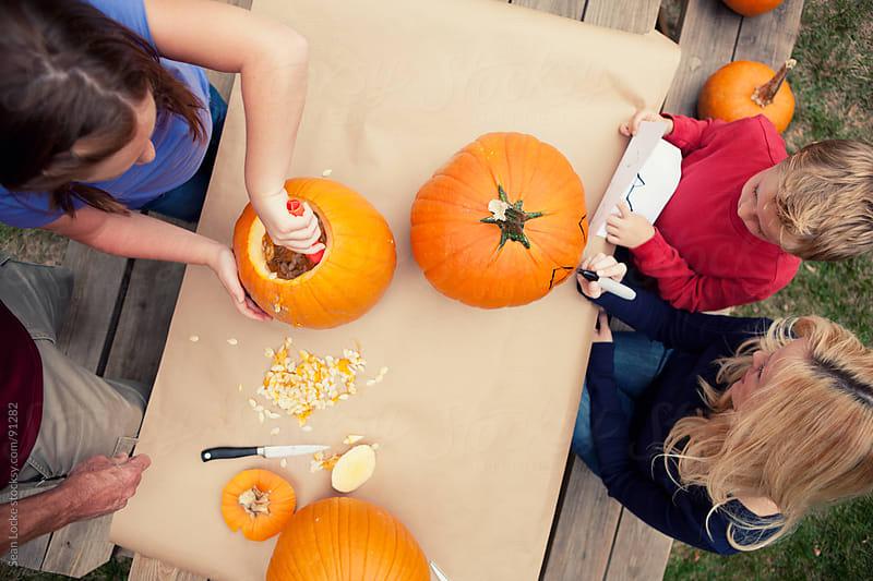 Pumpkins: Family Creating Halloween Jack-O-Lanterns by Sean Locke for Stocksy United
