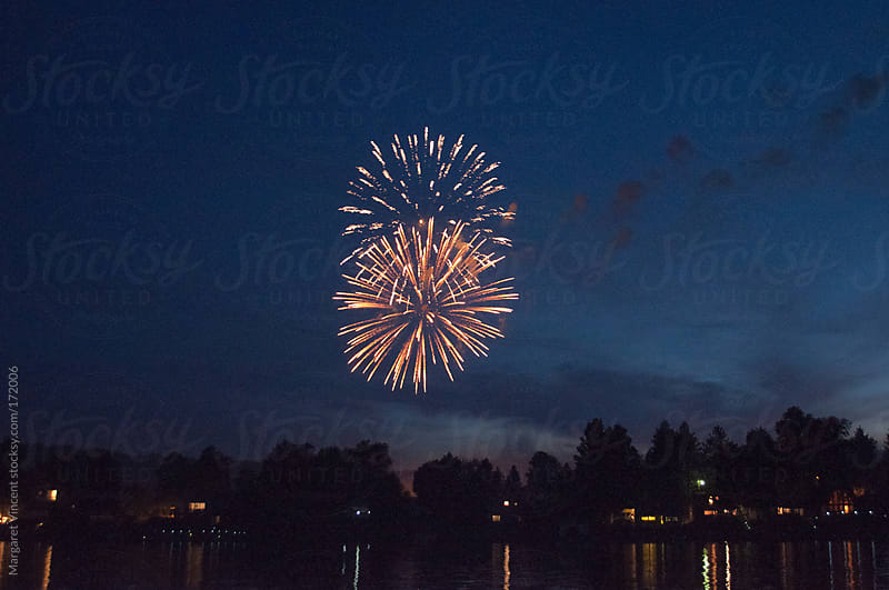 fireworks over a lake by Margaret Vincent for Stocksy United