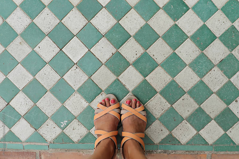 Woman standing on tiled floor by Preappy for Stocksy United