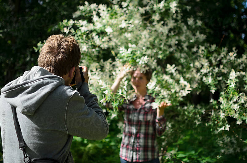 Photographer taking photo of a woman outdoors in the park by Alice Nerr for Stocksy United