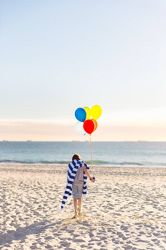 Boy walking at the beach holding a bunch of colorful balloons by Angela Lumsden for Stocksy United