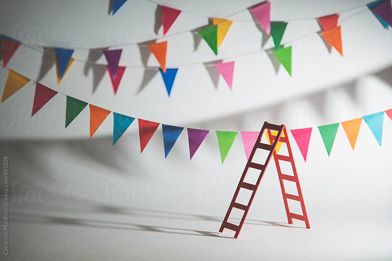 Hanging bunting in preparation for a celebration (horizontal) by Catherine MacBride for Stocksy United
