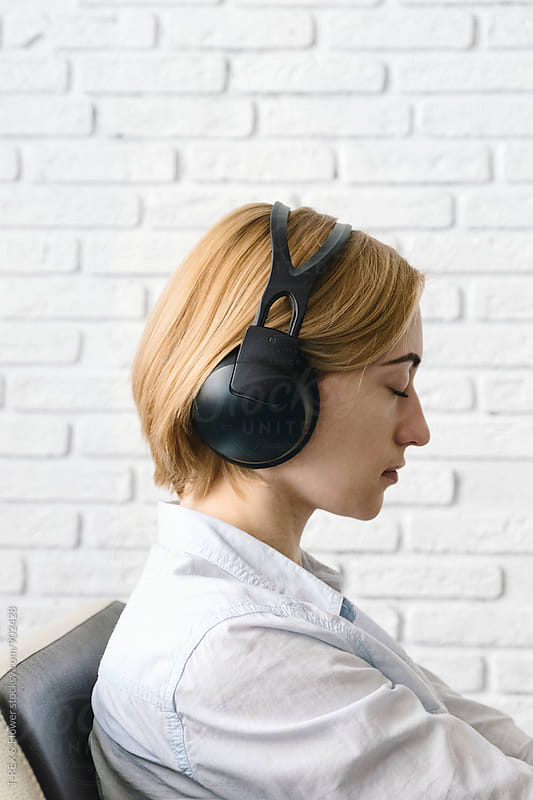 Woman listening to music in headphones by T-REX & Flower for Stocksy United