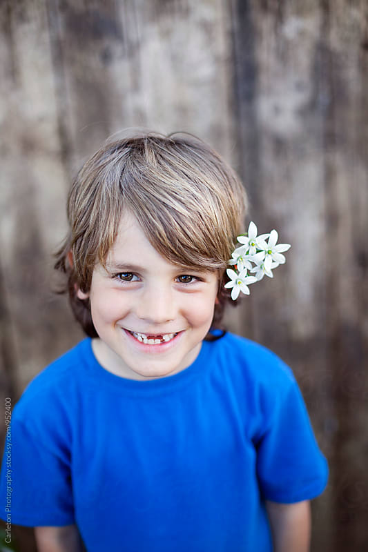Headshot of smiling seven year old boy with flowers in his hair by Carleton Photography for Stocksy United