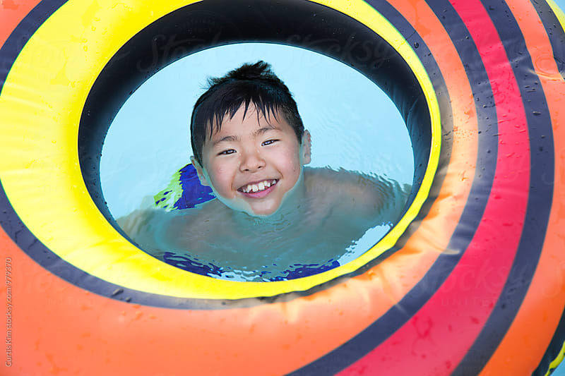 Young asian boy playing with inner tube by Curtis Kim for Stocksy United