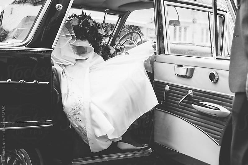 bride in white wedding dress getting out of an oldtimer car in black and white by Leander Nardin for Stocksy United