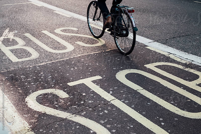 Person riding bicycles in London over the BUS STOP sign by Katarina Radovic for Stocksy United