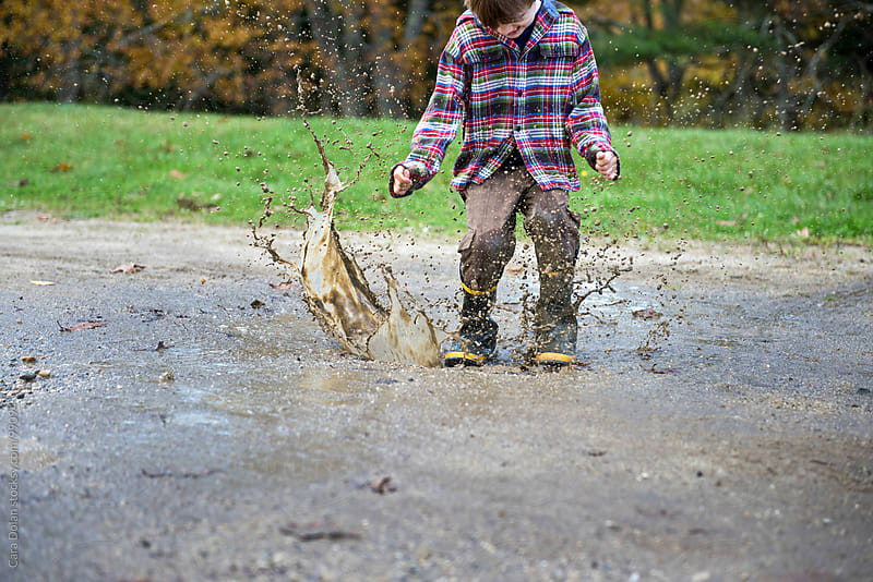 Boy wearing rubber boots splashes in a mud puddle by Cara Dolan for Stocksy United