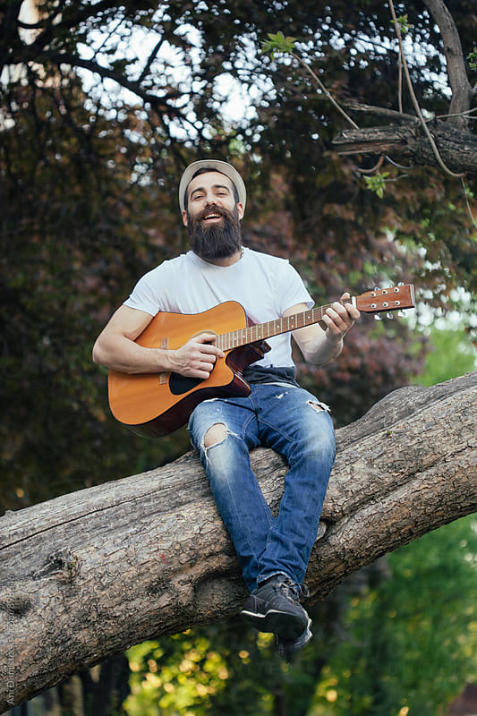 Man with a guitar sitting on a tree by Ani Dimi for Stocksy United