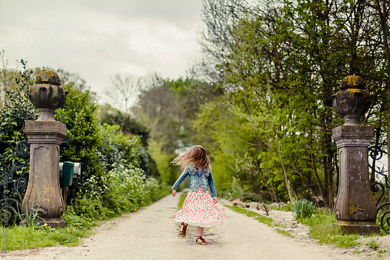 Little girl in flower dress twirling at the start of an entranceway by Cindy Prins for Stocksy United