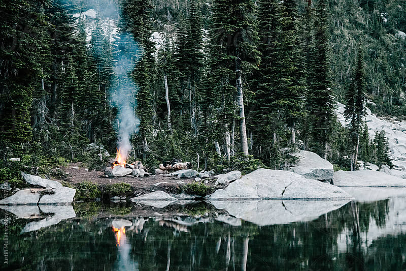 Campfire with plume of smoke beside calm mountain lake.  by Justin Mullet for Stocksy United