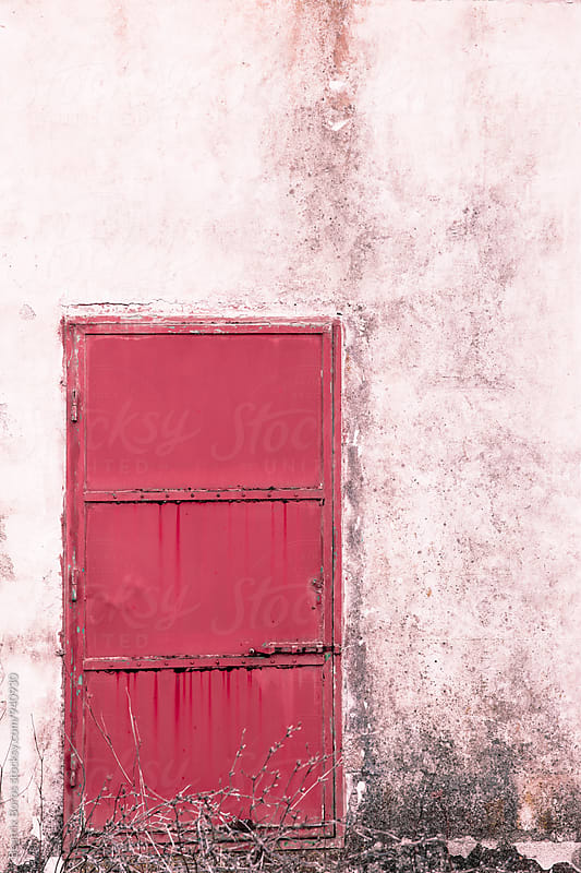 Pink iron door on pinkish wall of a building by Beatrix Boros for Stocksy United