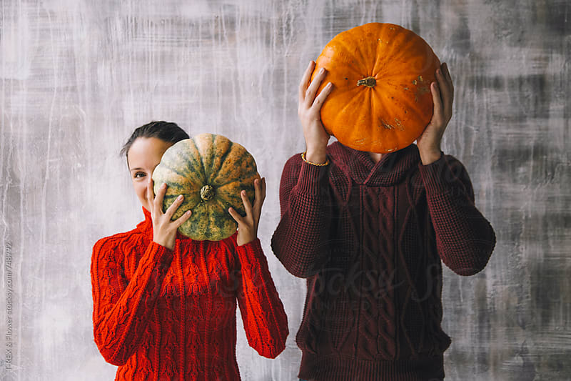 Couple holding pumpkins in front of faces by Danil Nevsky for Stocksy United