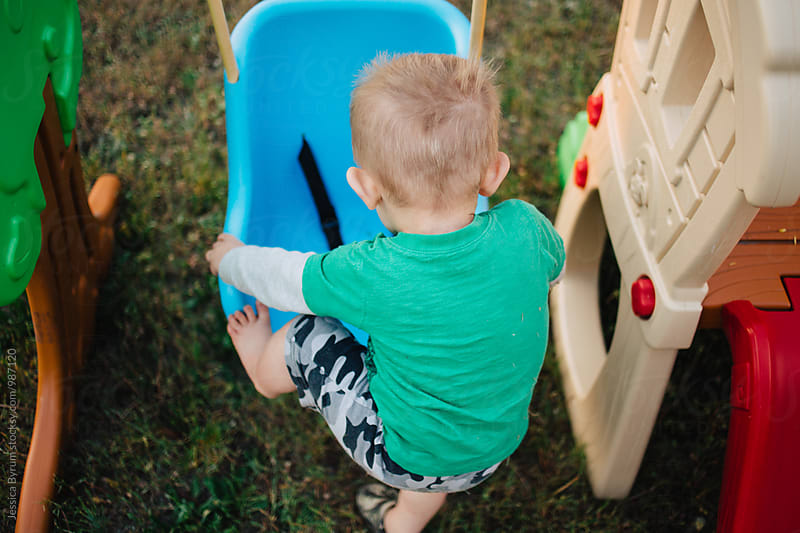 Toddler boy climbing on swing by Jessica Byrum for Stocksy United