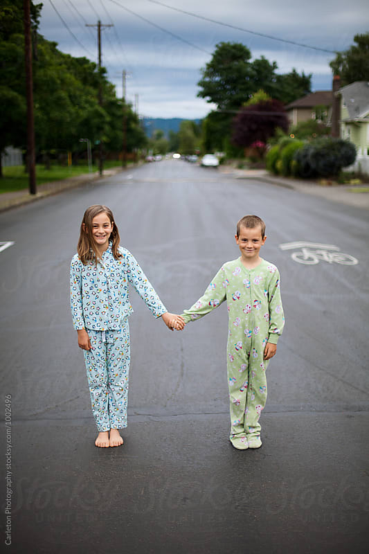 Sister and brother hold hands in the middle of a street in their pajamas by Carleton Photography for Stocksy United