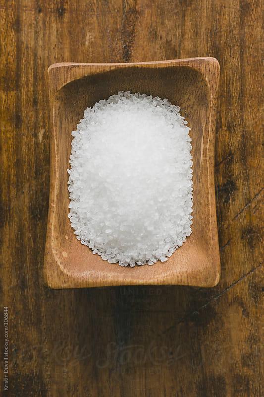 Sea salt in wooden salt cellar by Kristin Duvall for Stocksy United