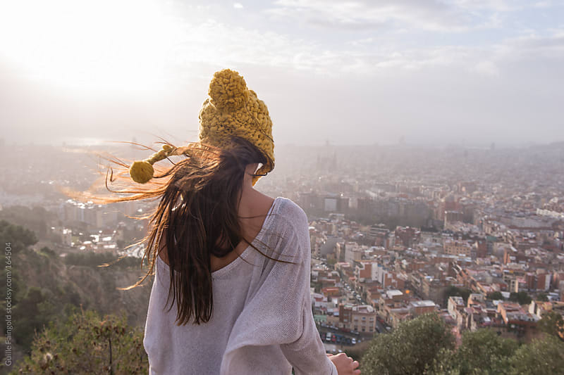 Back view of person with windy hair in hat viewing Barcelona city by Guille Faingold for Stocksy United
