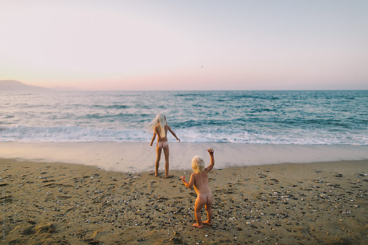 Two little naked sisters playing on the beach at sunset by