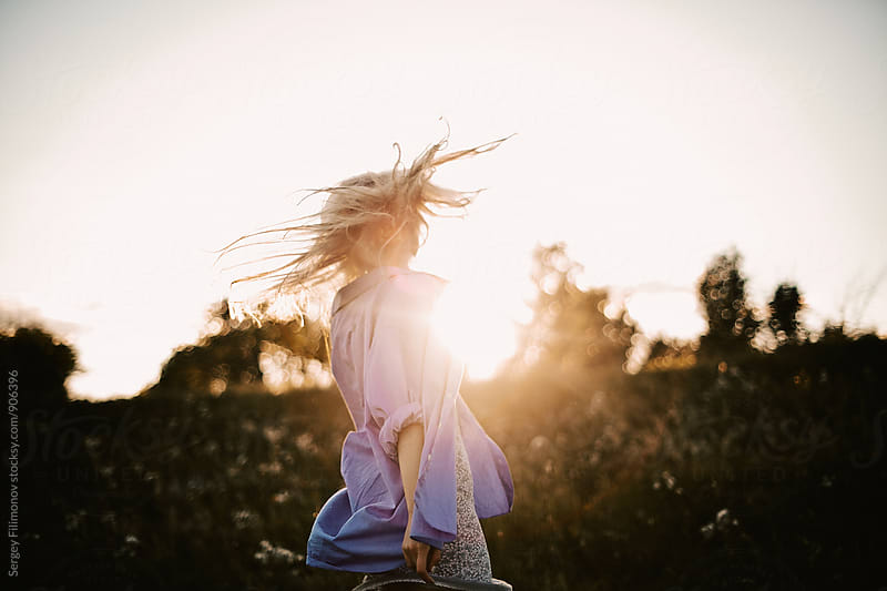 Young blonde girl  jumps in the field at sunset by Sergey Filimonov for Stocksy United