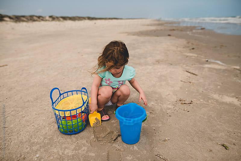 Girl digging at the beach by Courtney Rust for Stocksy United