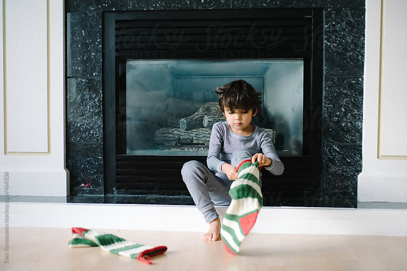boy wears puts Christmast stockings on his feet by Tara Romasanta for Stocksy United