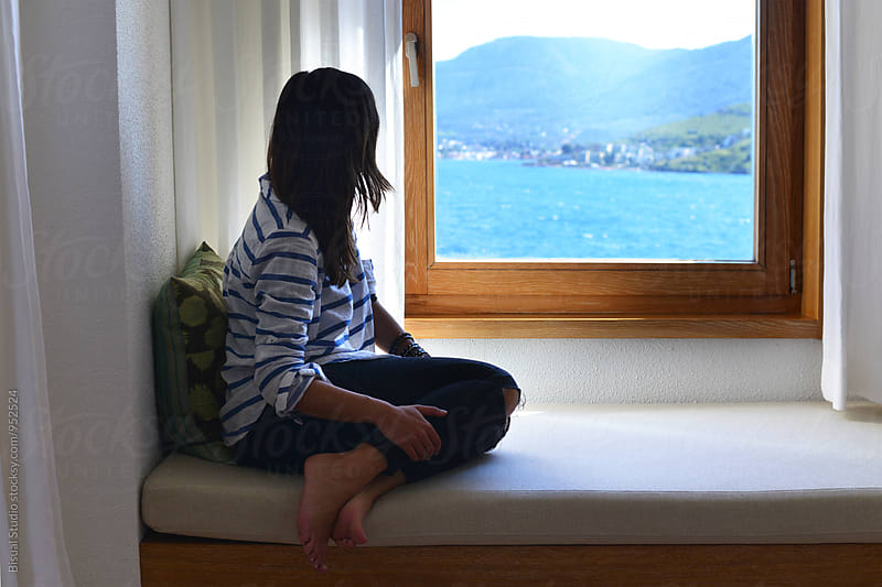 Young woman looking through the window to the Aegean sea by Bisual Studio for Stocksy United