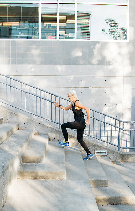 fitness woman stretches and exercises on cement staircase in urban city by Jesse Morrow for Stocksy United