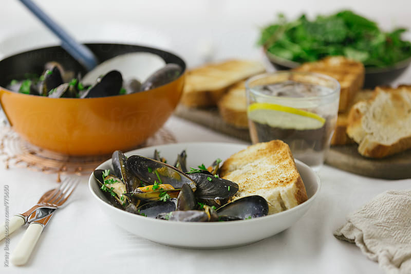 Dinner table with mussels and toasted bread by Kirsty Begg for Stocksy United