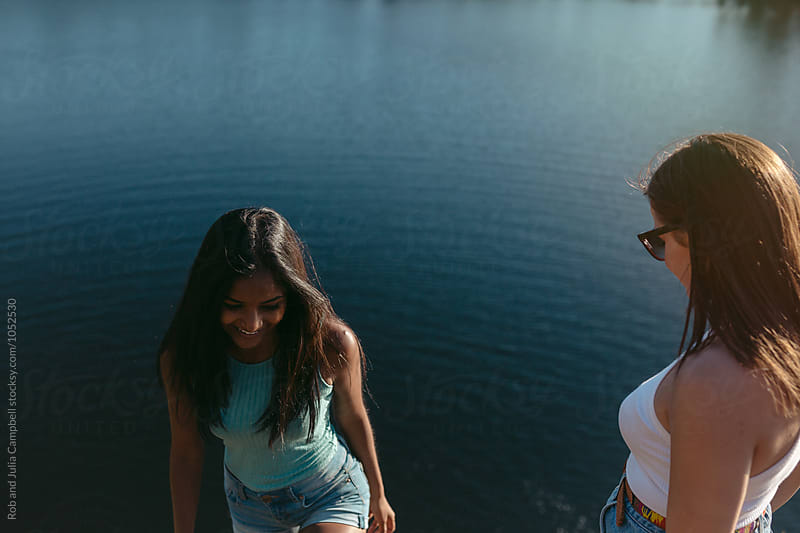 Young, happy girls hanging out by lake in summer by Rob and Julia Campbell for Stocksy United