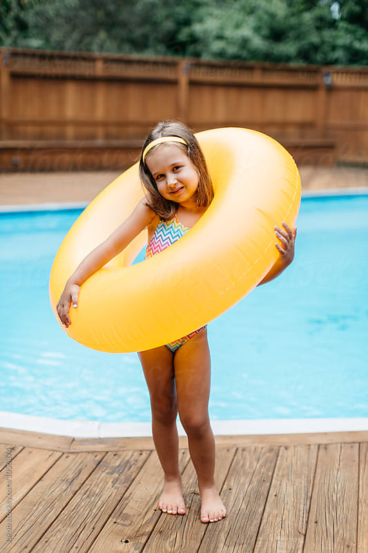 Sassy young girl standing by a pool with an inner tube by Jakob for Stocksy United