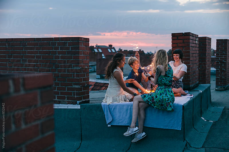 Young pople celebrating on a rooftop by VegterFoto for Stocksy United