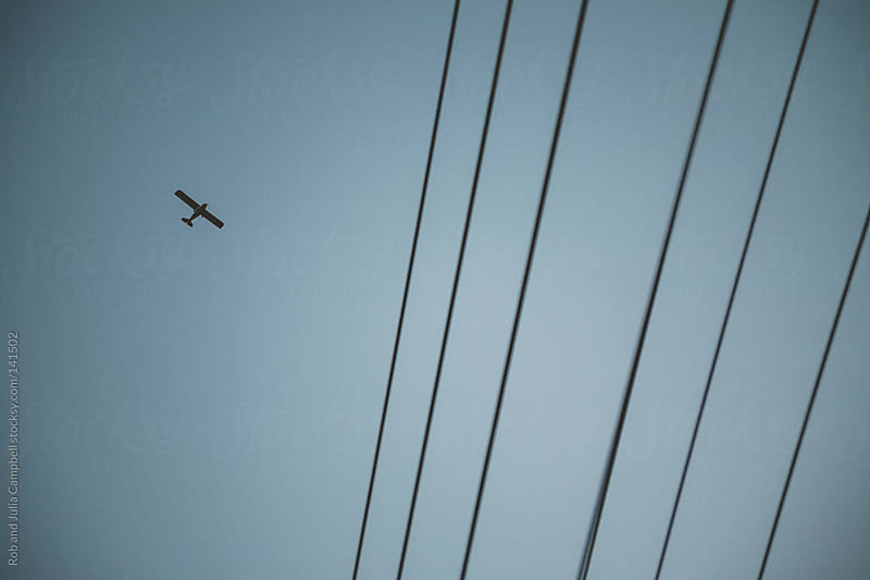 Airplane flying above telephone lines by Rob and Julia Campbell for Stocksy United