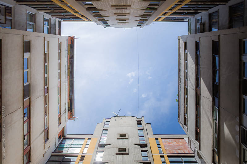 Worm's eye view between buildings by Jovo Jovanovic for Stocksy United
