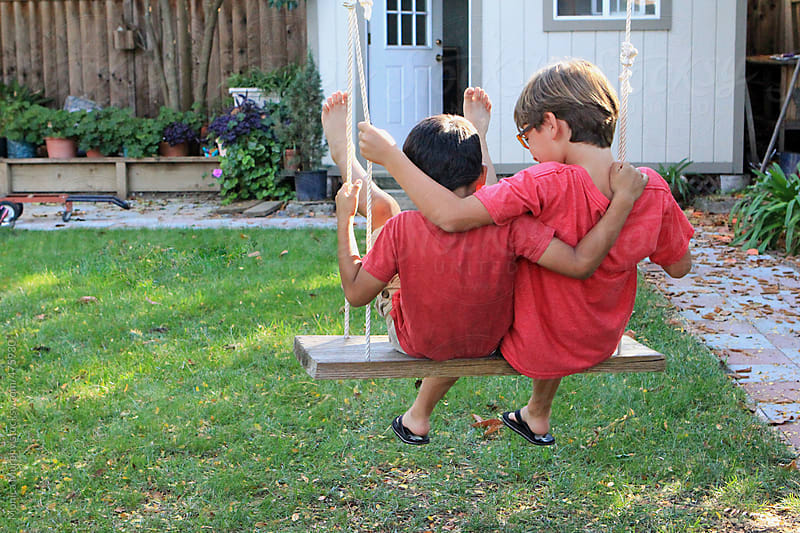Two friends swing together in backyard by Monica Murphy for Stocksy United