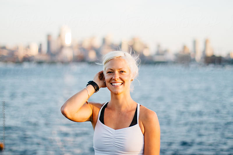 portrait of young fit female during work out routine in large city near water by Jesse Morrow for Stocksy United