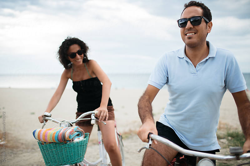 Young happy couple riding bikes on the beach by Davide Illini for Stocksy United