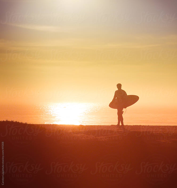 Silhouette of a surfer headed to the ocean at sunset by Carolyn Lagattuta for Stocksy United