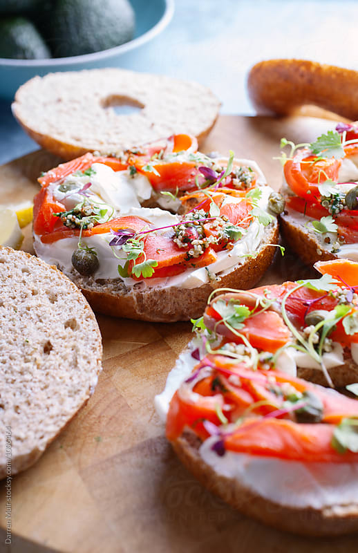 Wholemeal bagels with salmon and cream cheese.Preparing bagels. by Darren Muir for Stocksy United