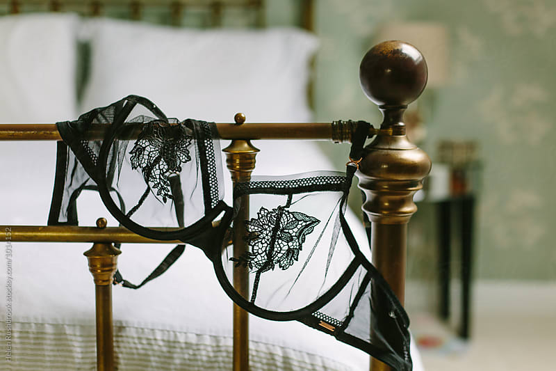 Black mesh bra draped over the end of a brass bedstead by Helen Rushbrook for Stocksy United