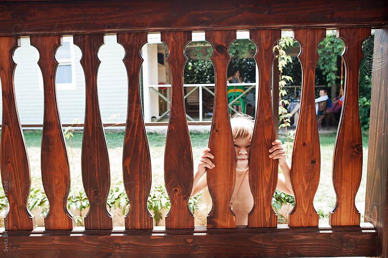 Little girl behind a wooden fence of porch by Svetlana Shchemeleva for Stocksy United