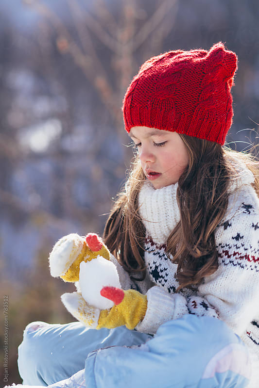 Girl making snowball. by Dejan Ristovski for Stocksy United