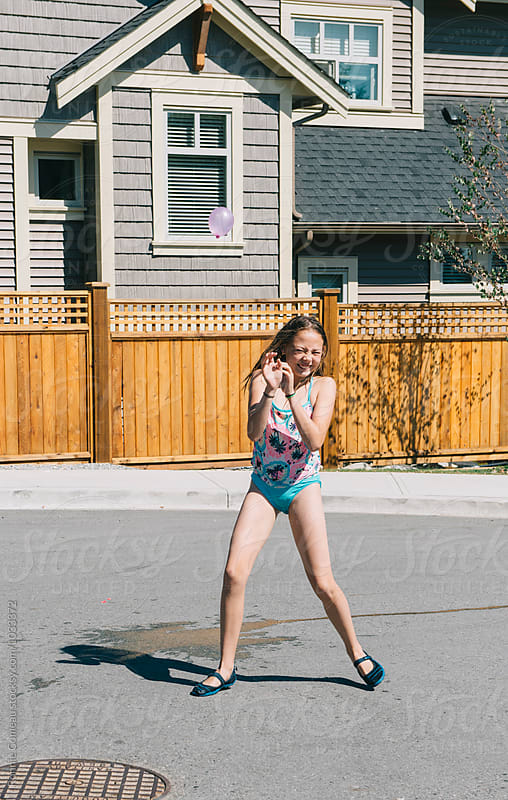 Girl Awaits Water Balloon by Ronnie Comeau for Stocksy United
