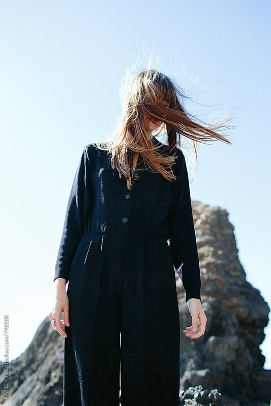 Girl standing on a windy beach with hair in her face by KATIE + JOE for Stocksy United
