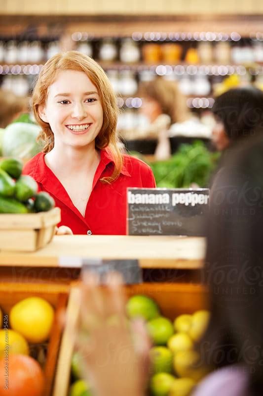 Market: Woman Sees Friend Over Grocery Bins by Sean Locke for Stocksy United